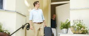 Mann verlässt mit Koffer das Haus und geht die Treppe hinunter.