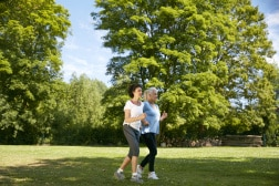 Zwei Frauen treiben im Park Sport.
